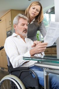 Wife with Husband In Wheelchair Reading Letter - Schiffman Law, P. C.